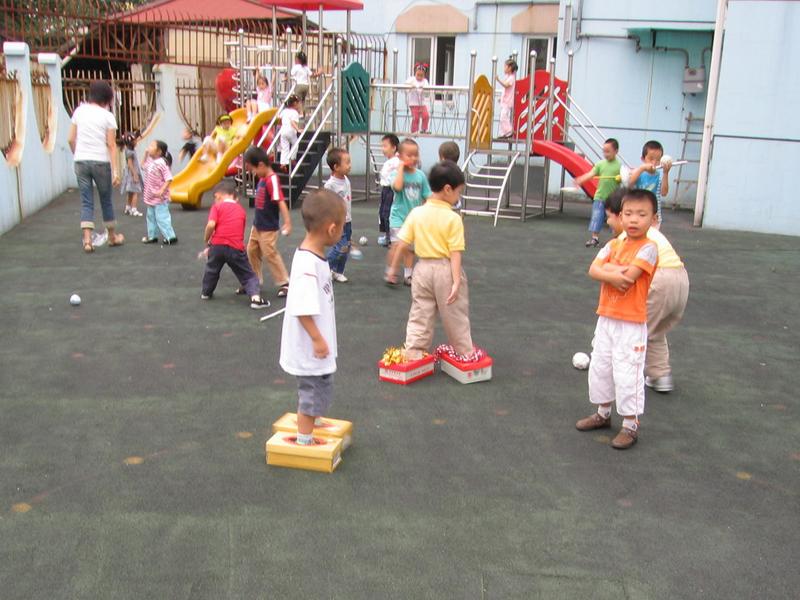 运动是孩子在幼儿园乐此不疲的一个环节。如何使孩子在玩的过程中大胆进行各种身体运动,体验各种肢体动作的,漕河泾幼儿园中班组的老师进行了尝试:她们发挥家长资源,根据中班孩子的年龄特点设计了小丑鞋和高尔夫两个自制体育器具,让家长用鞋盒和挂历纸、饮料瓶进行制作,让孩子进行运动和游戏。 果然有了器械和环境的创设,孩子们将走、跳、推、转、抛、接等动作通过小丑鞋和高尔夫等器械淋漓尽致地发挥出来,让孩子快乐地参与运动。同时,中班组老师在操节的编排上,结合庆祝奥运会的主题,将操节动作的编排以拉拉队的形式展现,
